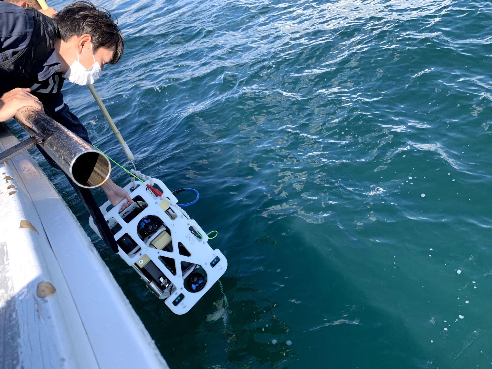 一人は水中ドローンを手で持ち、もう一人は先端にかぎ針のついた棒を使って、着水の衝撃を与えないように静かに投入します。